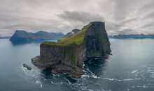 AERIAL: Flying Around Small Grassy Island With Scenic Mountains And Cliffs.
