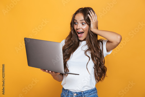 Fototapeta Portrait of charming woman 20s with long hair surprising and holding gray laptop