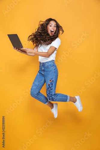 Fotografia Full length portrait of a pretty girl with long dark hair jumping