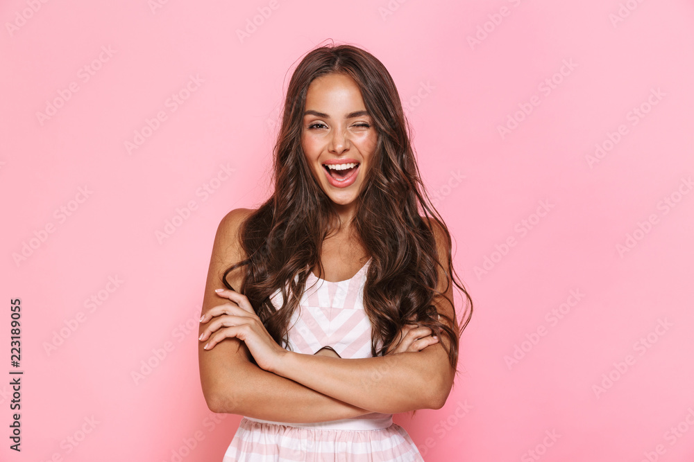 Fototapeta Image of cute woman 20s with long hair wearing dress smiling at camera with arms crossed, isolated over pink background