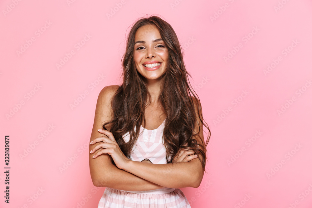 Fototapeta Image of european lovely woman 20s with long hair wearing dress smiling at you with arms crossed, isolated over pink background