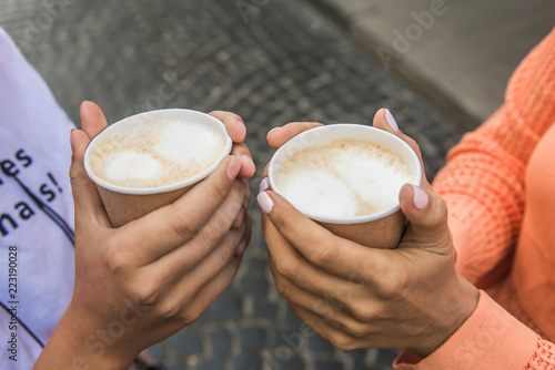 Foto op Plexiglas Chocolade two paper glasses with an armor and a milk foam hold the women's hands
