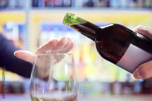Aluminium Prints Bar Woman hand rejecting more alcohol from wine bottle in bar