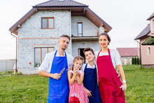 Rear View Of Parents With Children Son And Daughter Paitners In Aprons Hugging While Standing Together In House On Background. The Concept Of A Happy Family.