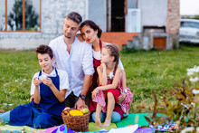 Rear View Of Parents With Two Children Son And Daughter Paitners In Aprons Hugging Together Sitting On Grass, Picnic Time Over Their House On Background. The Concept Of A Happy Family.