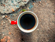 Red and white cup with dark coffee on the ground