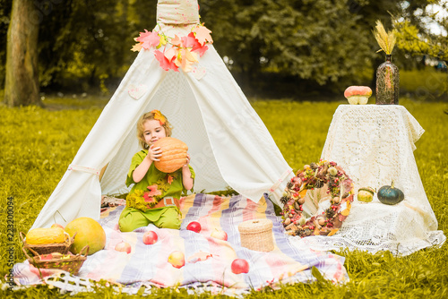 Photo Little girl lying and playing in a tent, children's house wigwam in park Autumn portrait of cute curly girl