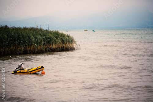 Fotografía  Dinghy with engine in the lake, yellow dinghy, reed