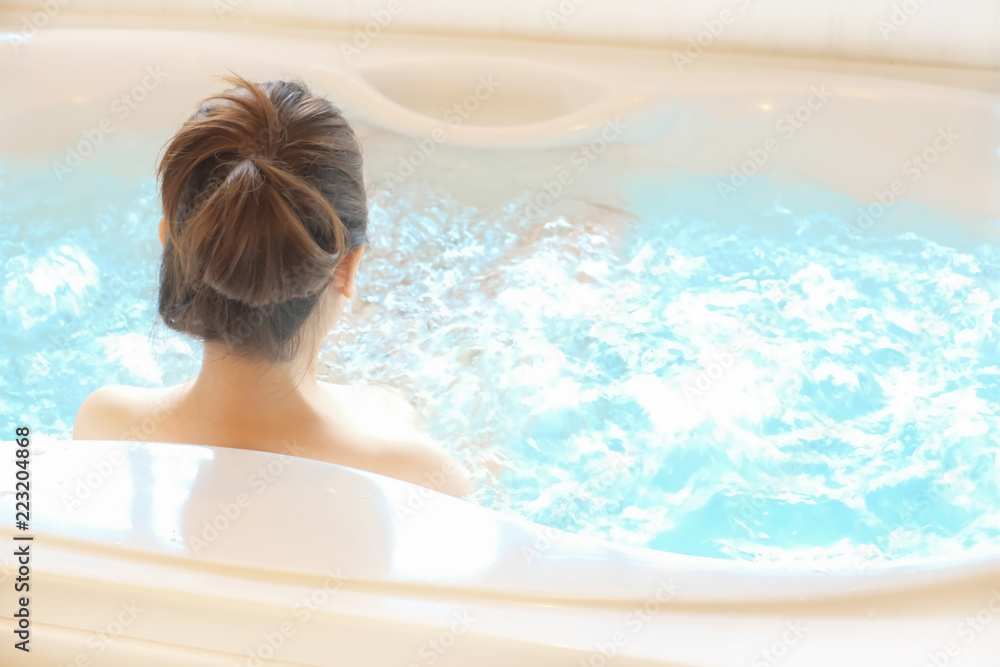 Fototapeta Beautiful spa. Back view of a young woman enjoying bathtub in a spa, space for design, Back view, Beauty concept.