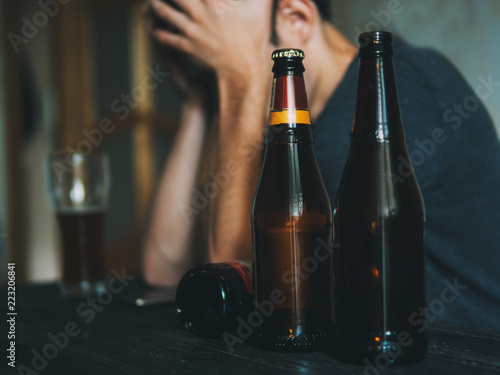 Fotobehang Bar A man addicted to alcohol. Hold hands on the head, the concept of loneliness
