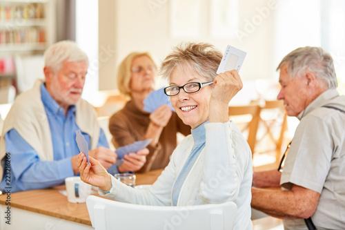 фотография  Ehrgeizige Senior Frau beim Karten spielen