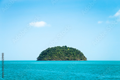 Round green island. Seascape with rock island in the tropical sea, Thailand.