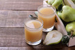 Pear juice in a glass with fresh ripe pears on a brown wooden table