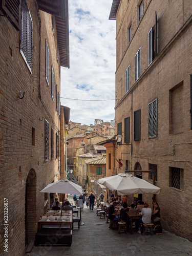 Poster Smal steegje italienische enge Gasse im Abendlicht mit Restaurants, Siena, Toskana, Italien