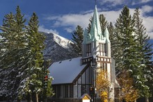 St. Paul Presbyterian Church In City Of Banff, Alberta With Distant Snowy Rocky Rundle Mountain In The Background