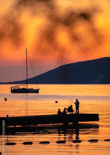 Spoed Foto op Canvas Zee zonsondergang Silhouette of people fishing on the sea at sunset. Beautiful sea sunset scene.