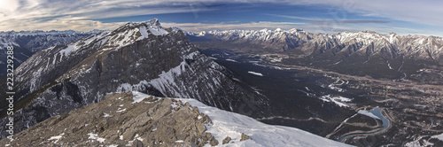 Scenic Wide Panoramic Landscape View of Bow Valley, City of Canmore and Distant Snowy Rocky Mountain Tops in Banff National Park from summit of Ha Ling Peak in Alberta Canada