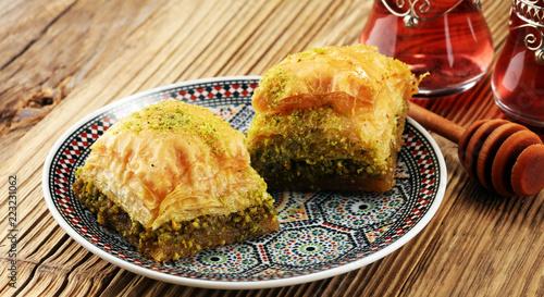 Photo Turkish Dessert Baklava with pistachio on wooden table.