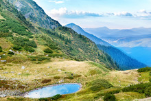 Blue Lake In The Mountains With Green Grass