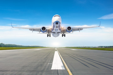 Passenger airplane landing at in good clear weather with a blue sky clouds on a runway.