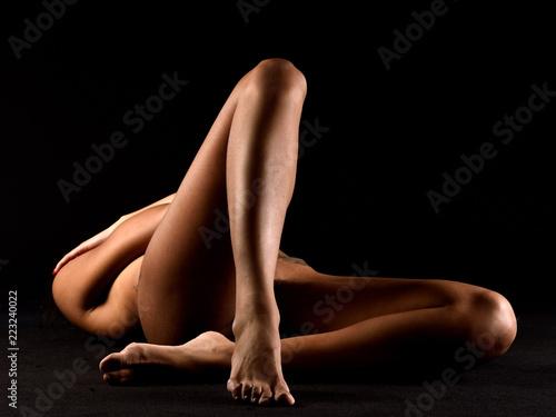 Staande foto Akt nudo artistico d'autore erotico di gambe nude abbronzate di donna nuda incrociate sexy erotche e sensuali