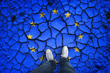 Top View Of A Person Standing On Damaged Cracked Soil Ground With Painted European Union Flag. Point Of View Perspective Used. Conceptual EU Disintegration Background.