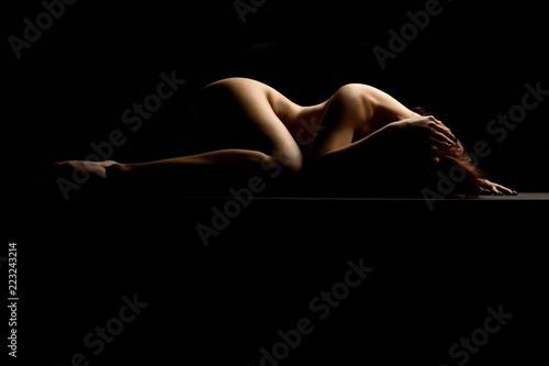 Nudo artistico di donna nuda sexy sensuale ed erotico distesa e sdraiata su specchio con il corpo mentre riposa