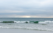 Wave Rolling In Towards Shore, Soft Light Blue Clouds, Sunshine On Horizon
