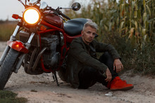 Stylish Brutal Hipster Man In A Fashion Military Jacket With Red Shoes Sits Near A Motorcycle With Light In The Evening In The Nature