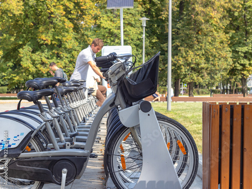 Fotografia  Automatic rental station and parking bicycle in the park, against the background