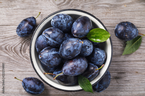 Metal bowl full of ripe prune fruit on a wooden table, top view