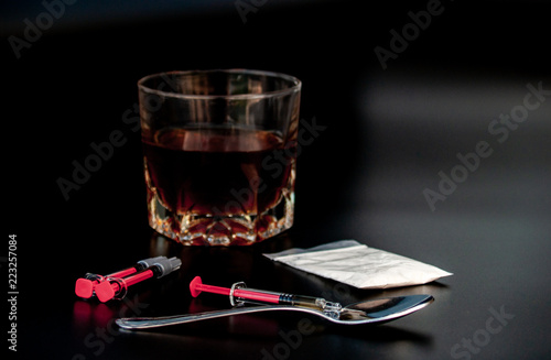 Fotobehang Bar Drug, one spoon, syringes and a glass of whiskey with black background. Drug and alcohol concept