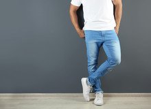 Young Man In Stylish Jeans Near Grey Wall With Space For Text, Focus On Legs