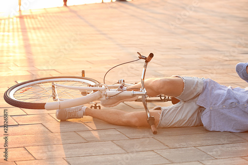 Man fallen off his bicycle on street, closeup