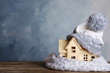 canvas print picture - Plywood toy house with warm hat, scarf and space for text against color background. Heating system