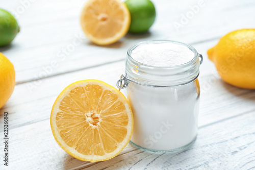 Jar with baking soda and lemon on white wooden table