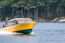 Colorful Bright Yellow Boat With American Flag Cruises Along The Damariscotta River In Maine