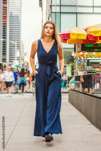Photo  Young Eastern European Woman with long brawn hair traveling in New York City, wearing blue sleeveless, v neck, jumpsuit, black leather shoes, walking on busy street in middletown of Manhattan