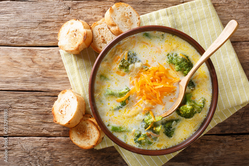 Healthy lunch broccoli cheese soup in a bowl with toast close-up. Horizontal top view