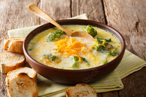 Traditional recipe of broccoli cheese soup with vegetables in a bowl with toast close-up. horizontal