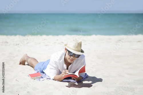 Cuadros en Lienzo Young Asian man happy smiling and read books on the beach