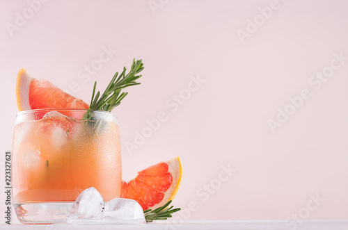 Cold grapefruit cocktail decorated twig rosemary and slice citrus closeup on pink background.