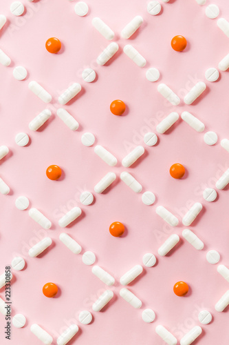 Fotobehang Macrofotografie Pattern of white and orange pills and tablets on a pink background.