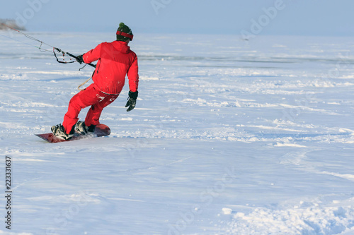kiting on a snowboard on a frozen lake