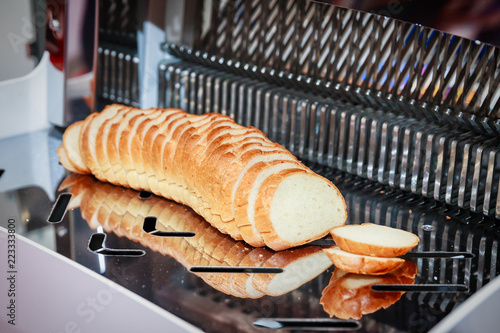 Obraz na plátně Automatic bread slicer with big sliced loaf