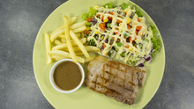 Grilled Kurobuta Pork Steak In Green Plate On A Black Rock Background. Props Decoration ,French Fries, Green Salad, Top View With Copy Space For Your Text..