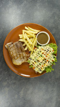 Grilled Kurobuta Pork Steak In Brown Plate On A Black Rock Background. Props Decoration ,French Fries, Green Salad, Top View With Copy Space For Your Text..