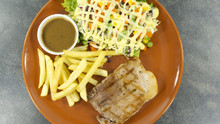 Grilled Kurobuta Pork Steak In Brown Plate On A Black Rock Background. Props Decoration ,French Fries, Green Salad, Top View With Copy Space For Your Text.