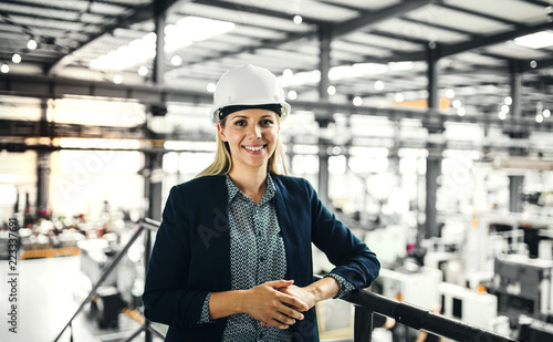 A portrait of an industrial woman engineer standing in a factory.