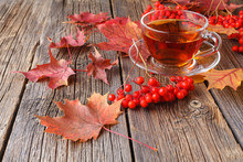 Cup Of Linden Tea With Autumn Leaves On A Wooden Background